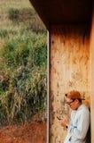 Jeune homme asiatique employant la position de téléphone portable contre l'esprit en bois de mur image libre de droits