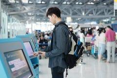 Jeune homme asiatique employant les kiosques auto- d'enregistrement dans l'aéroport Photos stock