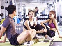 Jeune homme asiatique et femmes se reposant pendant l'exercice Images stock