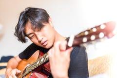 Jeune homme asiatique jouant la guitare espagnole à l'intérieur images libres de droits