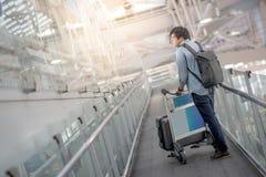 Jeune homme asiatique marchant avec le chariot dans le terminal d'aéroport Images libres de droits