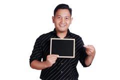 Jeune homme asiatique montrant le petit tableau noir Photos libres de droits