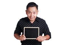Jeune homme asiatique montrant le petit tableau noir Photographie stock