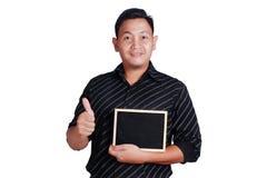 Jeune homme asiatique montrant le petit tableau noir Photo stock