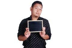 Jeune homme asiatique montrant le petit tableau noir Photos stock