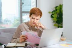 Jeune homme asiatique payant ses factures à la maison dans le salon Photographie stock libre de droits