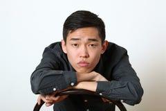 Jeune homme asiatique réfléchi regardant l'appareil-photo images stock