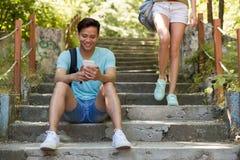 Jeune homme asiatique s'asseyant dehors sur l'échelle causant par le téléphone Photo stock