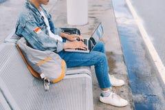 Jeune homme asiatique s'asseyant sur la chaise à l'arrêt d'autobus d'aéroport et Images libres de droits