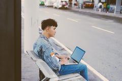Jeune homme asiatique s'asseyant sur la chaise à l'arrêt d'autobus d'aéroport et Photos stock