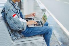 Jeune homme asiatique s'asseyant sur la chaise à l'usin de paiement d'aéroport Image stock