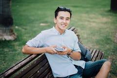 Jeune homme asiatique s'asseyant sur le banc en parc avec le téléphone dans h photo stock