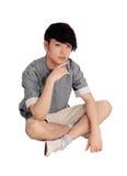 Jeune homme asiatique s'asseyant sur le plancher Photographie stock