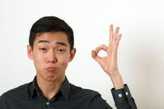 Jeune homme asiatique satisfaisant donnant le signe correct et regardant le Ca Photo libre de droits