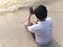 Jeune homme asiatique seul avec le téléphone intelligent mobile se reposant sur le sable de la plage tropicale photographie stock