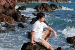 Jeune homme asiatique seul s'asseyant sur la roche du bord de mer image stock