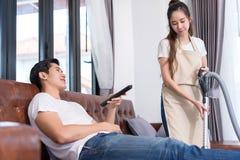 Jeune homme asiatique tenant la télévision de observation à distance photographie stock
