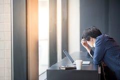 Jeune homme asiatique travaillant avec l'ordinateur portable dans l'espace de travail Photographie stock libre de droits