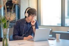 Jeune homme asiatique travaillant avec l'ordinateur portable dans l'espace de travail Photographie stock