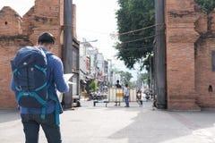 Jeune homme asiatique utilisant la veste bleue et les jeans lisant la carte tandis que Images stock