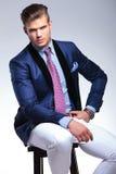 Jeune homme assis d'affaires avec la main à la hanche Image stock