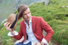 Jeune homme assis enlevant son chapeau Photo stock