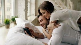 Jeune homme attirant à l'aide de la tablette se trouvant dans le lit tandis que son amie viennent l'étreindre dans la chambre à c Photographie stock