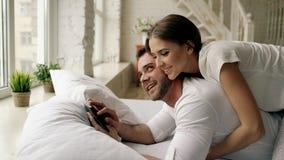Jeune homme attirant à l'aide de la tablette se trouvant dans le lit tandis que son amie viennent l'étreindre dans la chambre à c Images stock