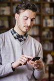 Jeune homme attirant dactylographiant au téléphone portable photographie stock libre de droits