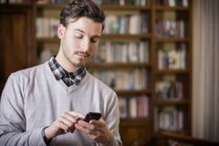Jeune homme attirant dactylographiant au téléphone portable, d'intérieur images libres de droits