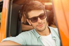Jeune homme attirant dans des lunettes de soleil se reposant sur un siège avant Photographie stock