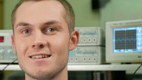 Jeune homme attirant dans la chambre avec le matériel électrique souriant à l'appareil-photo Dans la perspective d'un graphique d banque de vidéos