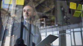 Jeune homme attirant de hippie vérifiant des diagrammes sur le conseil de verre clips vidéos