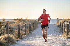 Jeune homme attirant et heureux de coureur de sport avec l'ajustement et la formation saine forte de corps sur outre de la voie d photographie stock libre de droits