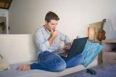 Jeune homme attirant et réussi travaillant du salon à la maison se reposant sur la mise en réseau de divan sur l'ordinateur porta photo stock