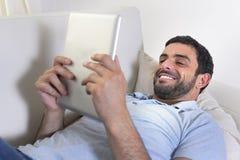 Jeune homme attirant heureux à l'aide de la protection numérique ou du comprimé se reposant sur le divan Image stock