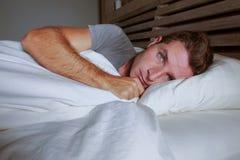 Jeune homme attirant inquiété agité éveillé la nuit se trouvant sur le lit sans sommeil avec le diso de souffrance ouvert large d photo stock