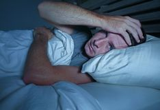 Jeune homme attirant inquiété agité éveillé la nuit se trouvant sur le lit sans sommeil avec le diso de souffrance ouvert large d photographie stock