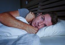 Jeune homme attirant inquiété agité éveillé la nuit se trouvant sur le lit sans sommeil avec le diso de souffrance ouvert large d photos libres de droits