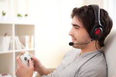 Jeune homme attirant jouant des jeux vidéo dans un sofa image libre de droits