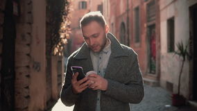 Jeune homme attirant marchant dans la ville et à l'aide du smartphone Mâle causant avec les amis et le café potable Photographie stock libre de droits