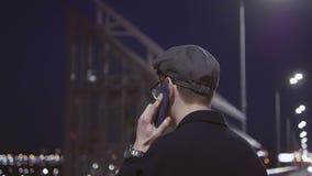 Jeune homme attirant parlant au téléphone tout en se tenant le soir dans une ville près de la rivière clips vidéos