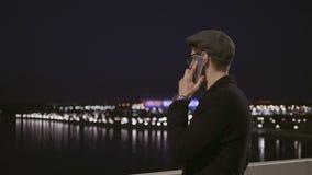 Jeune homme attirant parlant au téléphone tout en se tenant le soir dans une ville près de la rivière banque de vidéos