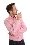 Jeune homme attirant réussi dans le rose semblant la participation latérale image stock