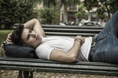 Jeune homme attirant se reposant sur le banc en bois Photos stock