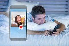 Jeune homme attirant se situant dans le lit sur la ligne recherchant le sexe ou l'amour trouvant un beau profil de fille envoyer  Images stock