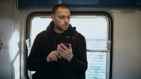 Jeune homme attirant se tenant dans la métro et à l'aide du smartphone Mâle beau surfant l'Internet dans le train clips vidéos