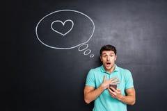 Jeune homme attirant stupéfait à l'aide du téléphone portable au-dessus du fond de tableau Image stock