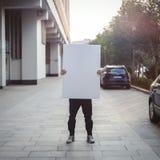 Jeune homme attirant tenant la toile vide à la rue Images stock