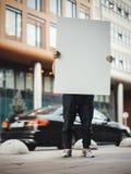 Jeune homme attirant tenant la toile vide à la rue à côté du bâtiment rouge Image libre de droits